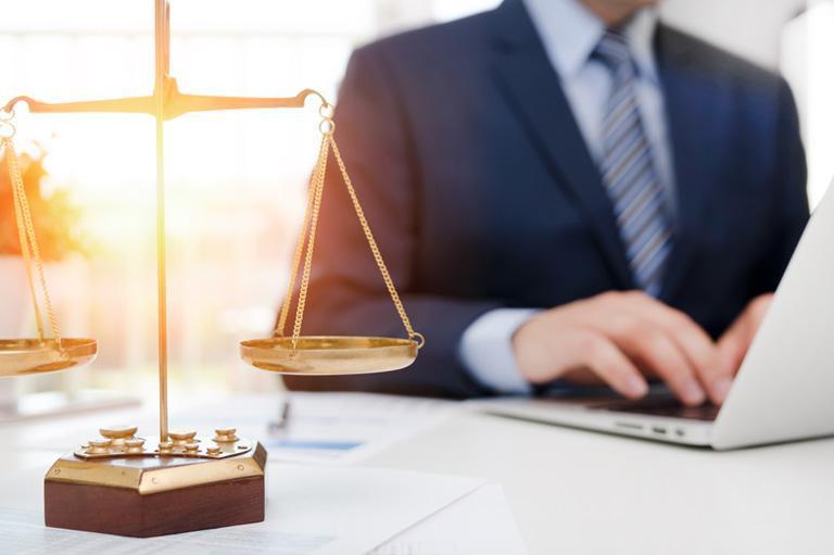 mężczyzna piszący nalaptopie iwaga adwokacka